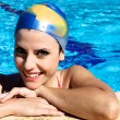Happy beautiful woman in swimming pool with cap smiling — Stockfoto