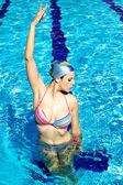 Beautiful woman doing gymnastics in the water in pool — Stock Photo