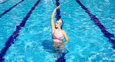 Synchronized swimmer in pool exercizing — Stock Photo