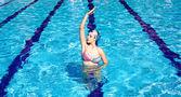Synchronized swimmer in pool exercizing — Stock Photo