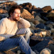 Handsome man relaxing on beach while working with tablet during sunset — Stock Photo
