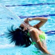 Beautiful woman having fun with water and hair in swimming pool — Stock Photo