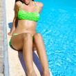 Happy female model in bikini laying on swimming pool — Stock Photo