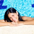 Beautiful female model smiling in swimming pool — Stock Photo