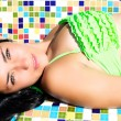 Fashion model with green eyes laying in bikini — Stock Photo