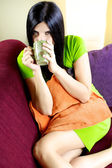 Happy relaxed woman on coloured sofa enjoying cup of tea — Stock Photo