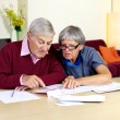 Senior family trying to do financial counts on bills — Stock Photo