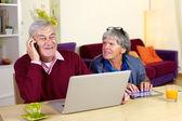 Mutlu büyükbaba evde oğluyla telefonda konuşurken — Stok fotoğraf