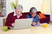 Senior couple in love with technology tablet and computer — Stock Photo