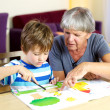 Happy grandmother doing homework with grandson — Stock Photo