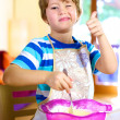 Thumb up for little happy kid cooking at home — Stock Photo