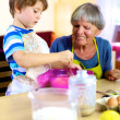 Happy grandmother helping grandson cooking cake — Stock Photo