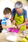 Senior woman helping grandson to cook and bake — Stock Photo