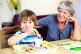 Happy child having snack during homework with smiling grandma — Stok fotoğraf