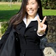 Happy smiling asian american girl with victory sign — Stock Photo #43263235