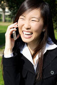 Happy asian woman on the phone laughing — Stock Photo