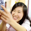 Cute asian american woman in bed taking selfie smiling — Stock Photo