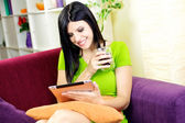 Happy woman relaxing at home with coffee and tablet — Stock Photo