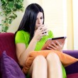 Relaxing with tablet and coffee at home reading news — Stock Photo #43908401