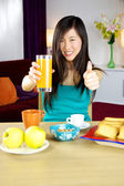 Cute asian woman having healthy breakfast with fruit and orange juice — Stock Photo