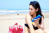 Female model posing with sun cream on sunny beach — Stock Photo