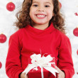 Little girl sitting in front of a christmas tree — Stock Photo