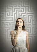 Maze. Girl in white solving a problem. — Stock Photo