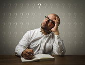 Man in white and question marks. — Stock Photo