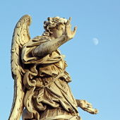 Bronze statue of an Angel, in Rome, with a pale moon in the sky — Stock Photo