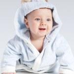 Portrait of a cheerful child in blue bathrobe — Stock Photo