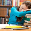 Sleeping girl in library — Stock Photo