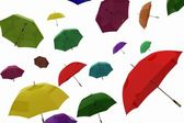 Flying of multicoloured umbrellas on a white — Stock Photo