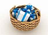 Gift boxes in a braiding basket on a white background — Stock Photo