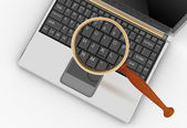 Laptop and magnifying glass. — Stock Photo