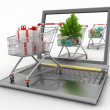 Concept of Christmas online shopping. Laptop computer  with festive shopping carts — Stock Photo