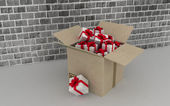 Cardboard box with gifts on brick wall background. — Stock Photo