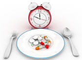 Pills on a dinner dish with a spoon and fork. Conception of reception of pills on hours. — Stock Photo