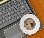 Coffee cup and saucer with a globe on computer keyboard on wooden table background — Stock Photo