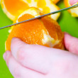 Woman cutting an orange — Stock Photo