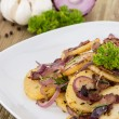 Portion of fried Potatoes with raw ingredients — Stock Photo