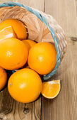 Oranges in a basket on wood — Stock Photo