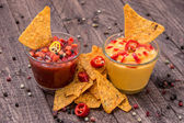 Salsa- and Cheese Sauce on wooden background — Stock Photo