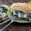 Herring Filet on a baguette (against wood) — Stock Photo