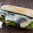 Fresh Herring with Onions on a baguette — Stock Photo