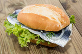 Fresh Herring on a roll (wooden background) — Stock Photo