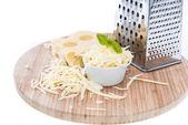 Emmentaler met kaas rasp op wit — Stockfoto