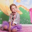 Little girl sitting on a pink floor — Stock Photo #16819277