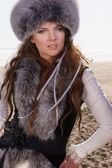 Young woman in a fur hat near the winter sea — Stock Photo