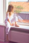 Little girl sitting near the window — Stock Photo