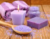 Purple sea salt and a burning candle — Stock Photo